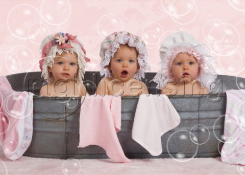 Three toddlers in flowery bonnets