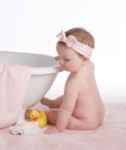 Baby with pink bow on towel